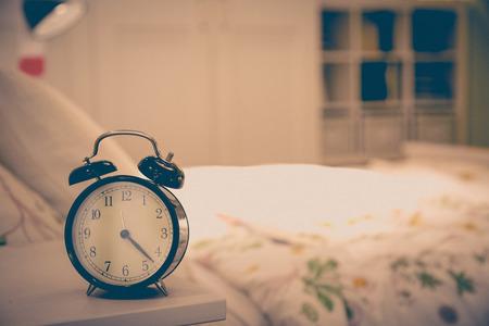 Alarm clock,on bedside with blur bed background Banco de Imagens