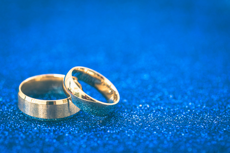 Gold wedding rings of bride and groom on dark blue gliter background