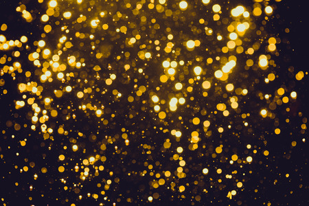 Abstract gold defocused bokeh of lights in dark background Stock Photo