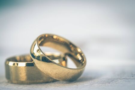 Golden rings, wedding rings of the bride and groom on white vintage wooden background Stockfoto