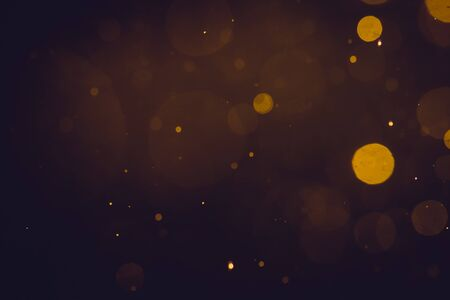 Dark Abstract Gold bokeh sparkle on black background