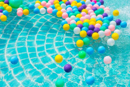 Colorful balls in the swimming pool reflecting the turquoise light