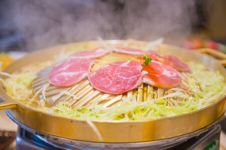 Pork slides grill food in a brass pan with cabbage vegetable