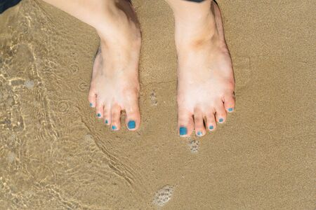 The womans foot nailed the sand on the beach.