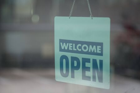 Open and welcome sign broad through the glass of window to let customers know