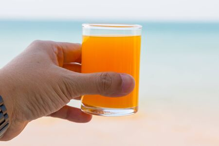 hand holding the full glass of orange juice with sea view background
