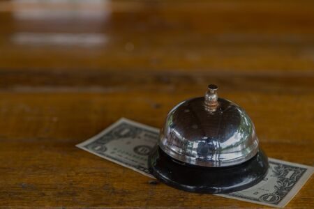 Bell on the table with money background