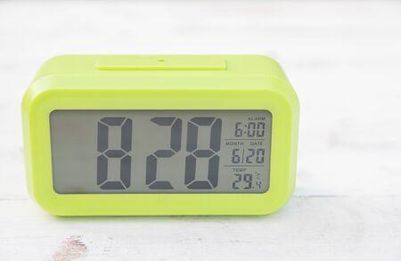 Light green digital clock on vintage wooden panels
