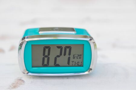 Light blue digital clock on vintage wooden panels