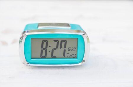 Light blue digital clock on vintage wooden panels Stock Photo - 125211077