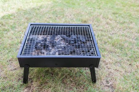 Empty grill with pile of charcoal outdoor background Stock Photo