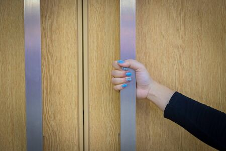 Woman's hand painted bright blue nails is opening the door. Banco de Imagens