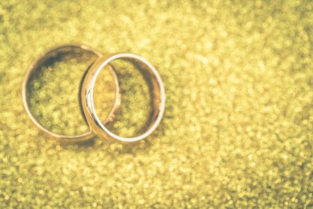 Gold wedding rings of bride and groom on gold glitter background Standard-Bild - 129453506