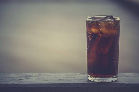 Cola con ghiaccio nel bicchiere pronto da bere per rinfrescare sullo sfondo sfocato