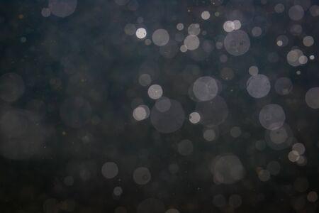 Bokeh fantasia scintilla dalla luce su sfondo nero