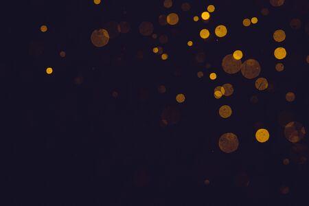 Fantasy gold bokeh sparkle from light on black background