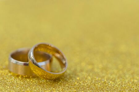 Gold wedding rings of bride and groom on gold gliter background