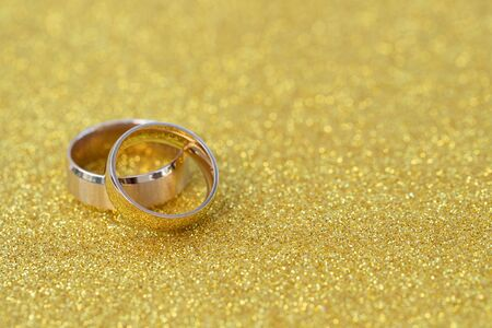 Golden rings, wedding rings of the bride and groom on white vintage wooden background Stock Photo