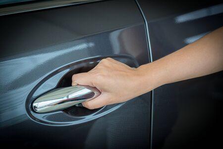 Woman hand on open the new car door background