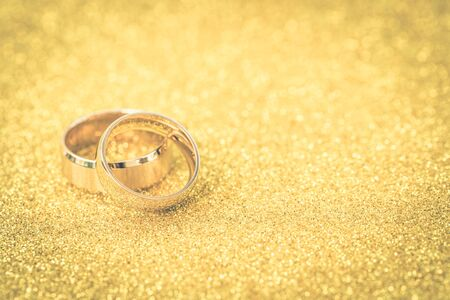 Golden rings, wedding rings of the bride and groom on white vintage wooden background Banque d'images