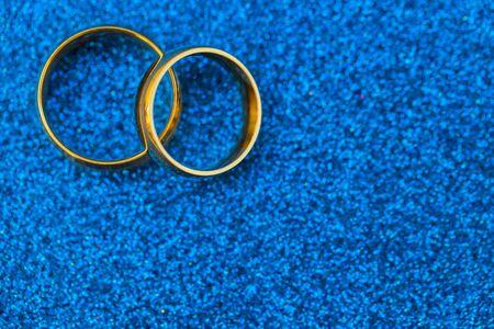 Gold wedding rings of bride and groom on dark blue gliter background