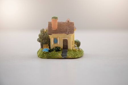 Model of house painted yellow under the tiled roof isolated on the blur natural background. Reklamní fotografie