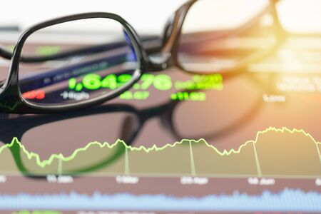 financial chart stock trading seen by unfocused glasses background
