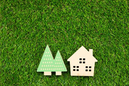 Small wooden house with tree on artificial grass as a top view background Reklamní fotografie