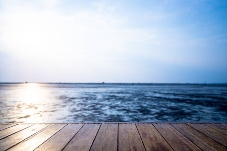 The wood floor extends into the sea when the water drops with sunset background Reklamní fotografie