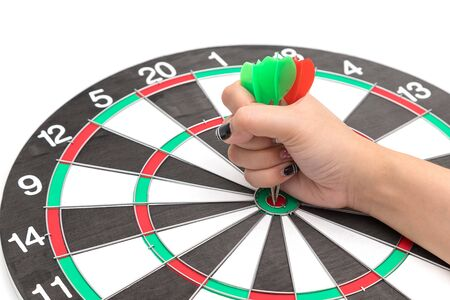 Hands with darts at the target center on a white background
