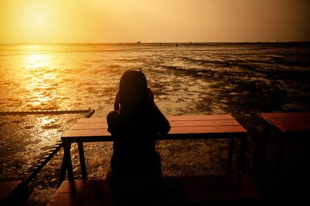 Women sitting and watching the sea at sunset nature background