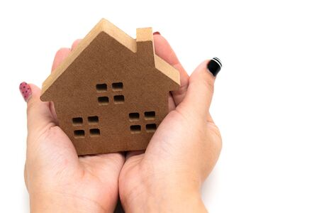 The concept of private housing,Two hands that hold the family home safe from danger