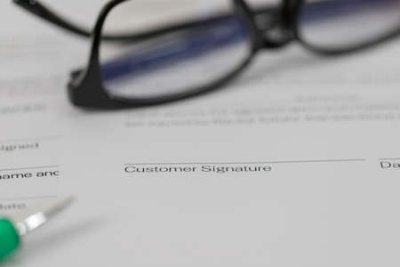 Sign on contract document with fountain pen and glasses on white background Banque d'images
