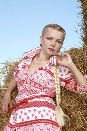 allurement: The girl with a plait near straw in a red shirt and a beads from pearls against the blue sky in the summer