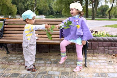 d?a: El ni�o peque�o da una flor amarilla a la ni�a en el parque en un banco en lago de verano  Foto de archivo