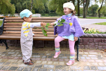 gives: The little boy gives a yellow flower to the girl in park on a bench at lake summer