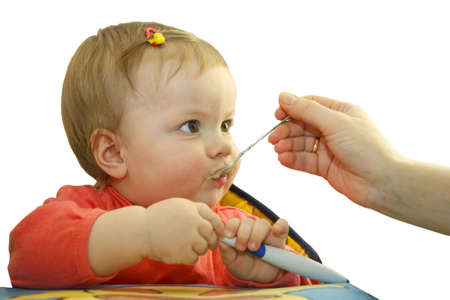 The child with a hairpin in hair sits at a table and he is fed with mum Stock Photo - 6752961
