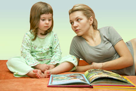 Mum reads the book to the child dressed in a pyjamas photo