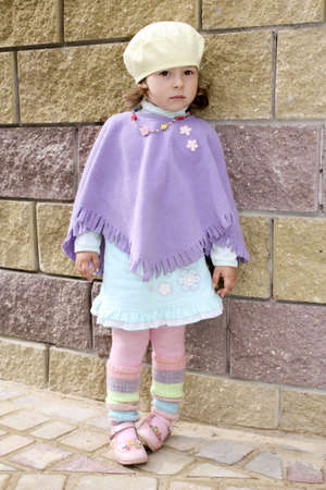 gaiters: The girl in a beret gaiters with a beads costs to a skirt near a stone wall