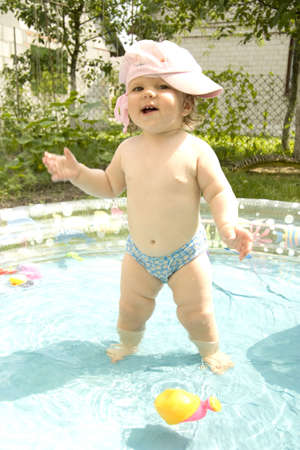 without clothes: The child in shorts and a cap costs in the summer in water and swings hands Stock Photo