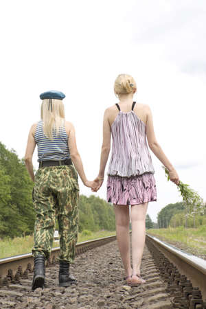 hand rails: The woman in the military form goes on rails and holds a hand of the woman in a dress with a bouquet