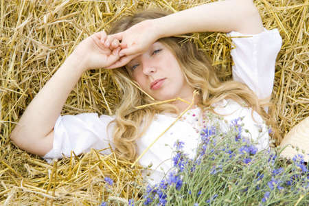 woken: woman lays on straw with a bunch of flowers in the summer and only has woken up Stock Photo