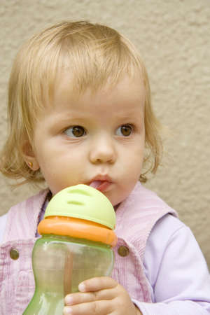 little girl drinks from a small bottle and with interest looks aside photo