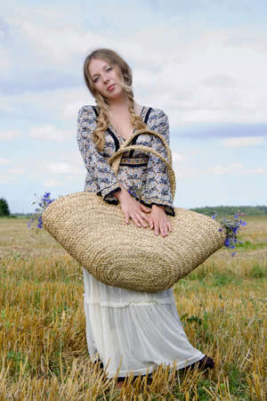 closes eyes: woman in a white skirt closes eyes and holds a basket with flowers on a shoulder Stock Photo