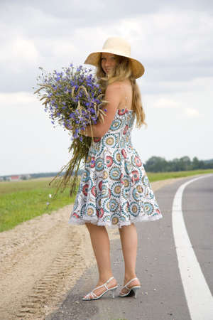 brink: The woman in a hat with a bouquet of cornflowers costs on the brink of road and looks back Stock Photo