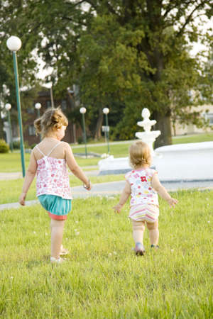 Two girls walk in the summer on a lawn Stock Photo - 7692193
