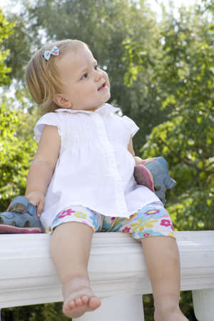 parapet: The small barefoot girl sits in the summer on a parapet and swings to legs Stock Photo