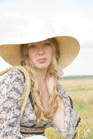 uncombed: The girl with uncombed hair in a hat sits in the summer in the field of