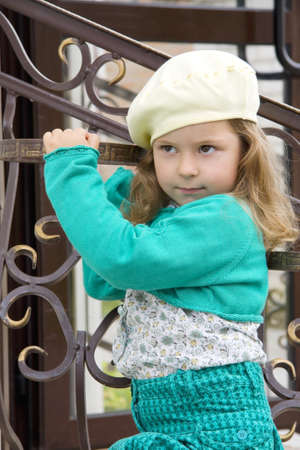 frowned: The girl in a yellow beret costs near the forged handrail in the summer and looks from under a forehead Stock Photo