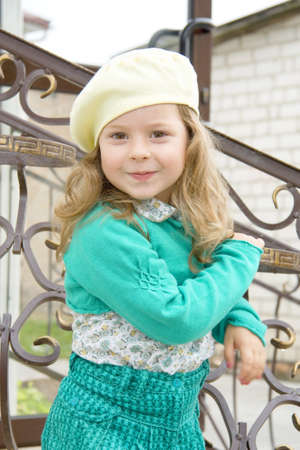 keeps: The joyful child on white in a yellow beret keeps hands for a fencing Stock Photo